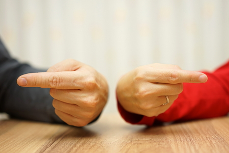 relation: adult couple has difficulties in relationship an both shows the finger at himself and herself Stock Photo