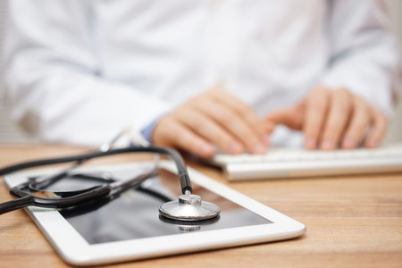 health answers: Blurred doctor in background typing on computer keyboard with tablet and stethoscope in foreground