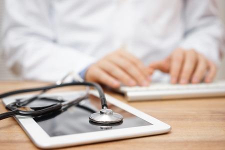 Verschwommene Arzt im Hintergrund Eingabe auf Computer-Tastatur mit Tablet und Stethoskop im Vordergrund