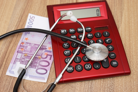 hospital expenses: Expensive health care concept with calculator,money and stethoscope Stock Photo