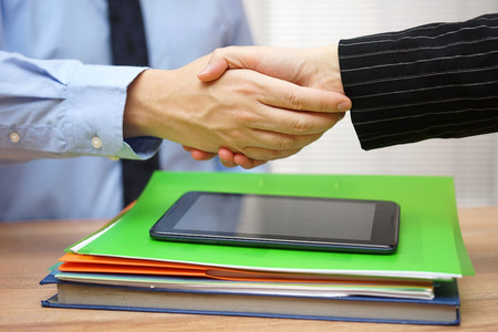 signed: Business partners are handshaking  over business documentation,collaboration concept
