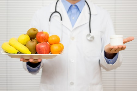physician: Doctor nutritionist  offers patient to choose between healthy  fruit or pills