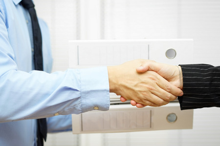adequacy: businessman and businesswoman are handshaking after exchanging binders Stock Photo