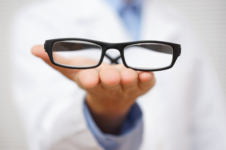 oculist: doctor oculist   offering  a pair of eyeglasses. concept of good vision