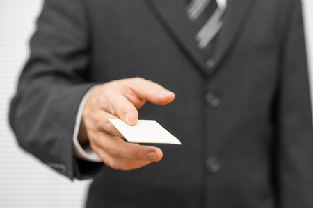 Business man handing a blank business card Banque d'images