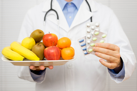 doctor holding healthy fruit  in one hand and pills in other hand,choosing between fruit or vitamin tablets