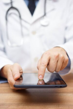 working on computer: doctor is working on tablet computer Stock Photo