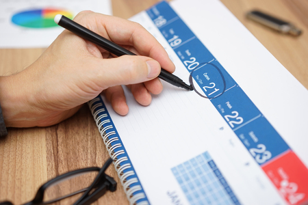 De zakenman is het instellen van een belangrijke datum op een kalender met een marker. Concept van plannen, organiseren, het belang Stockfoto