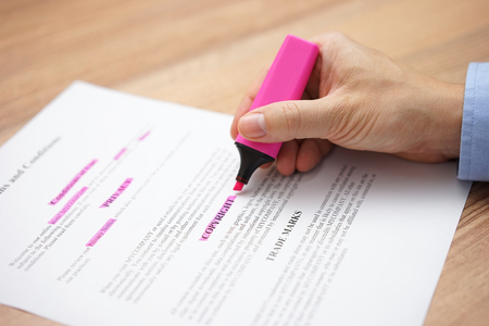 person is reading and marking text with highlighter in document