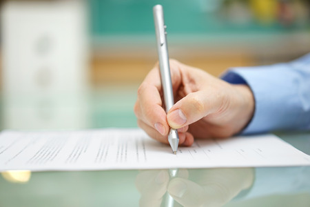 mans hand schrijft document thuis op het bureau Stockfoto
