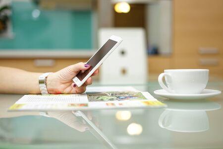 De vrouw leest het tijdschrift en surfen op het internet op slimme mobiele telefoon in de keuken