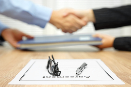 businessman and businesswoman are shaking hands and exchanging folder  after agreement was reached Stockfoto