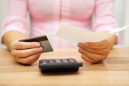 Frau hält Rechnung und Kreditkarte in der Hand und die Berechnung der Kosten