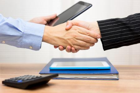 mensen uit het bedrijfsleven handshaking na het bekijken van zakelijke gegevens en informatie over de tablet-computer