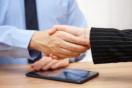 Zakenman handen schudden met partner na herziening van de activiteiten op de tablet-pc