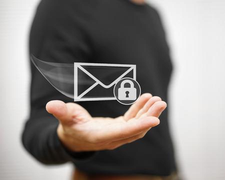 Young adult holding flying envelope witch padlock, secure communication concept Standard-Bild