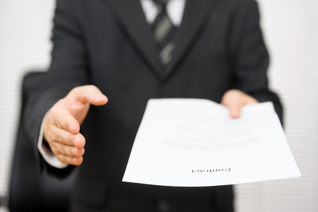 Businessman is offering his hand and contract to make a successful deal