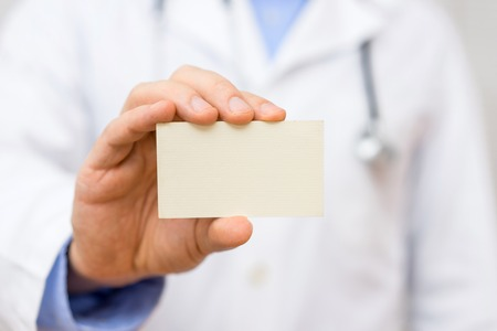 Doctor holding blank business card
