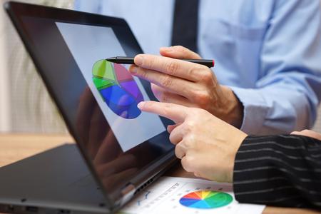 business team werkt tijdens de vergadering over het verslag met financiële diagram op laptop scherm, wijst met de vinger op de grafiek Stockfoto