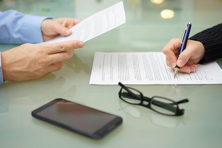 Geschäftsmann und Frau lesen und Vertragsabschluss