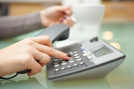 Frau drückt Taste auf am Telefon Wähltastatur und Kaffee trinken Lizenzfreie Bilder