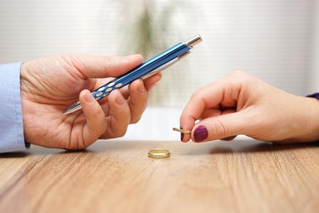 El marido está dando pluma para firmar los papeles del divorcio a su ex esposa después de despegar el dedo en forma de anillo Foto de archivo