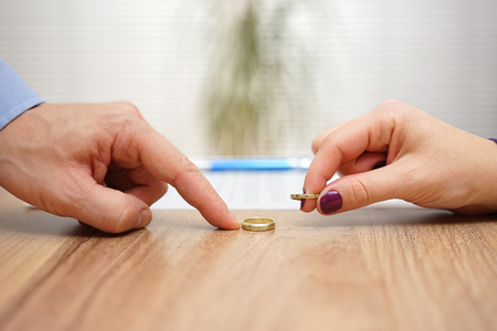 taking a wife: husband and wife are returning wedding rings,divorce concept Stock Photo