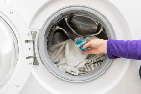 Woman pouring washing liquid, into the washing machine Standard-Bild