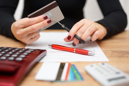 Frau schneidet Kreditkarte oder Bankkarte mit einer Schere über Vertrag und andere Kreditkarten