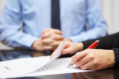 Frau ist die Unterzeichnung Vertrag mit Business-Mann im Hintergrund