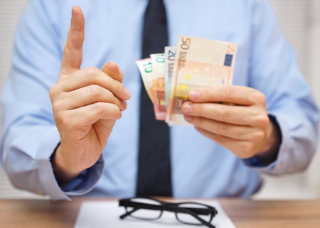 Manager warnt den Mitarbeiter, während er ihm Geld gibt Lizenzfreie Bilder