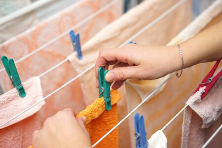 woman hands hanging clothes to dry on clothes-line after laundry