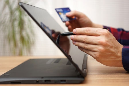 man gebruikt bankpas of creditcard om online te betalen op draagbare touchscreen laptopcomputer met pen