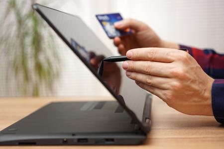 Mann ist mit EC-Karte oder Kredit mit Stift online auf tragbaren Touchscreen-Laptop-Computer zu zahlen