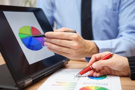 Die Geschäftspartner arbeiten gemeinsam an statistischen Daten Tablet-Computer und Papier Bericht mit