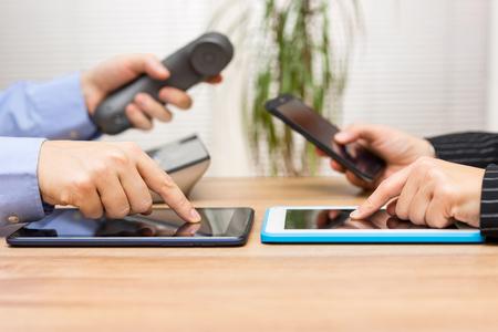 mensen uit het bedrijfsleven met behulp van tablet-computers tijdens de vergadering en het gebruik van telefoons voor communicatie