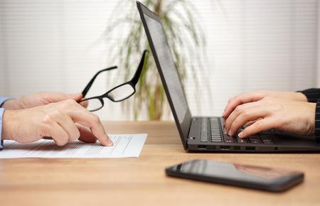twee partners onderzoeken en beoordelen van documenten in het kantoor, vrouw is met behulp van laptop voor commentaar