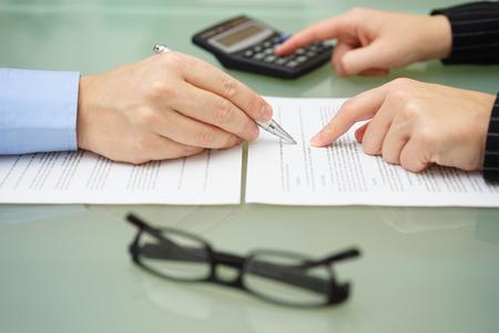 zakenvrouw is herzien document met belastingadviseur en het maken van berekeningen om verslag te optimaliseren