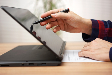 Student is taking on line course on touchscreen laptop computer or digital tablet with stylus pen