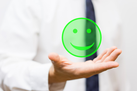 businessman is holding virtual smiley in his hand, concept of happiness and satisfaction