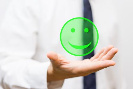 zakenman houdt virtuele smiley in zijn hand, het concept van geluk en tevredenheid