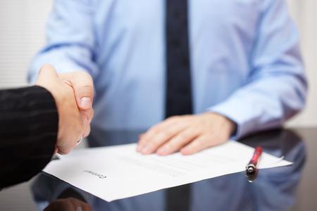 Unternehmer und Unternehmerin Händeschütteln über unterzeichneten Vertrag, Partnerschaftskonzept Lizenzfreie Bilder