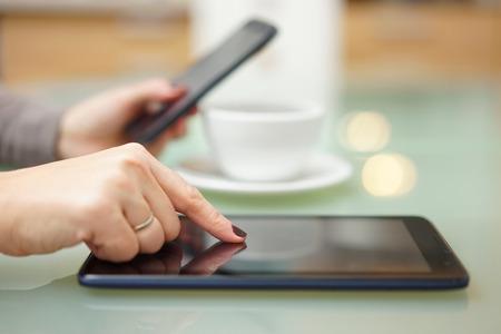 Vrouw is met behulp van tablet-pc en smartphone in de keuken op hetzelfde moment Stockfoto
