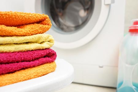 detersivi: asciugamani lavati impilati con lavatrice in background