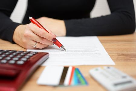 Frau liest Bank Mitteilung über Kreditkarte Ausgaben und Rückzahlung von Schulden