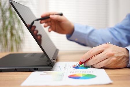 Geschäftsmann Analyse von Geschäftsdaten auf dem Dokument und die Arbeit mit Stylus-Stift auf dem Touchscreen Laptop-Computer Lizenzfreie Bilder