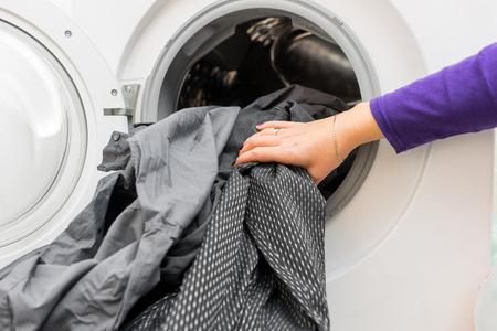 vrouw 's handen putting vuile kleren in de wasmachine Stockfoto