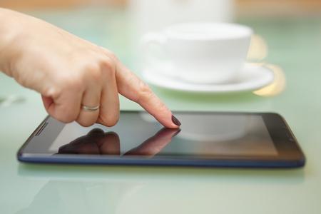 Close-up van de vrouw met behulp van tablet-computer thuis met een kopje koffie in de achtergrond Stockfoto