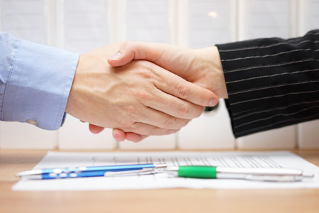 signed: businessman and businesswoman are handshaking over signed contract with binders in background Stock Photo