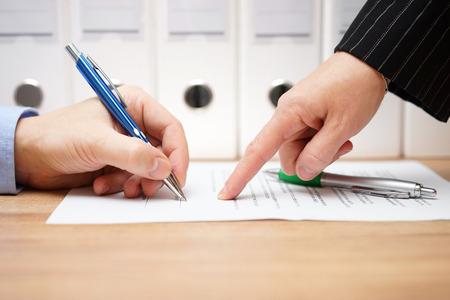 zakenvrouw wijst waar te ondertekenen document, met documenten op de achtergrond
